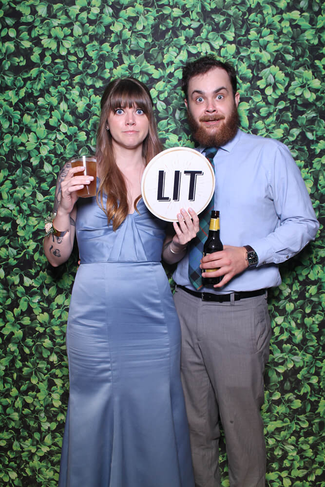 a couple poses with props in the photo booth