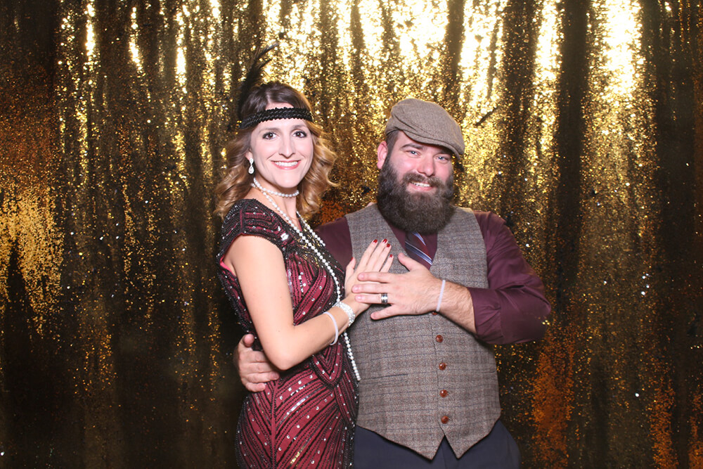 a couple poses in front of a gold backdrop at a 1920's Gatsby themed event.