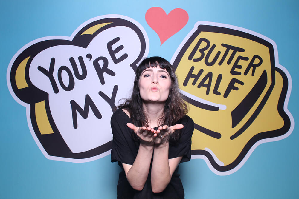 a woman poses in a photo booth in front of a You're my Butter Half backdrop