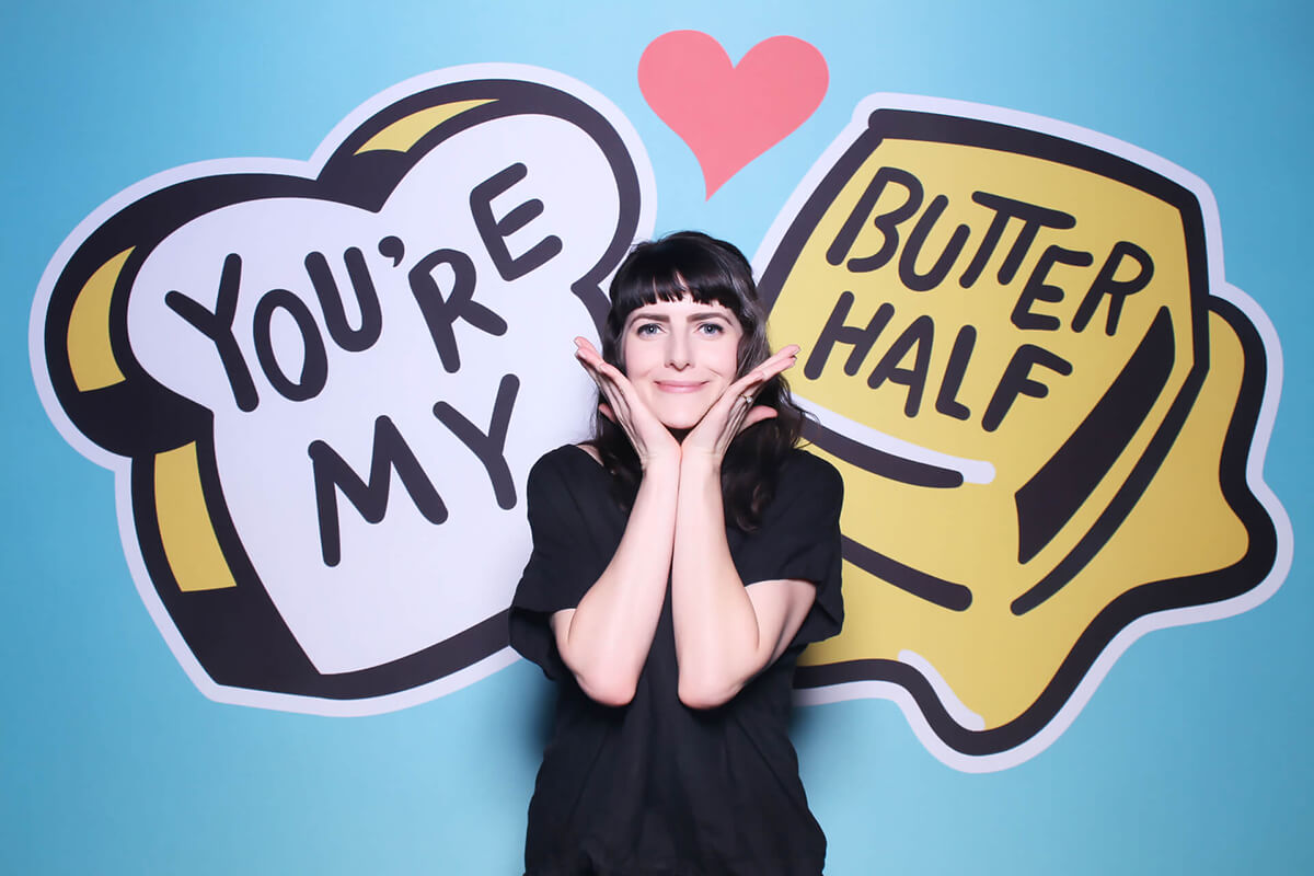 Woman posing in front of You're my Butter Half Backdrop in photo booth